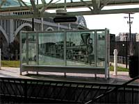 photo of a bus bench with glass windows around it