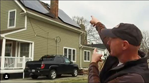 man pointing to a house that has solar panels on the roof